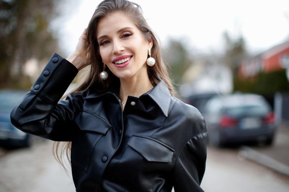 Cathy Hummels in schwarzer Lederjacke bei einem Fotoshooting auf der Straße