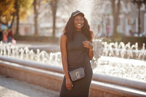 Crossbody-Tasche: Der Trend 2021, junge Frau vor Brunnen