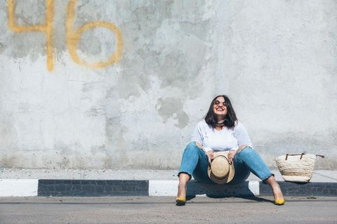 Mode-Einzelstück: Frau sitzt glücklich auf der Bordsteinkante