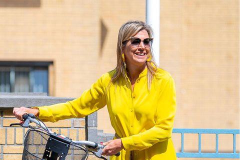 Let the sunshine in! Königin Máxima strahlt in ihrem gelben All-Over-Look gute Laune aus. Zu einer 7/8-Hose tailliert sie ihre Bluse mit einem Fransengürtel und trägt flache Ballerinas - so lässt sich die Fahrradtour zum Kunstmuseum in Den Haag einfacher bestreiten.
