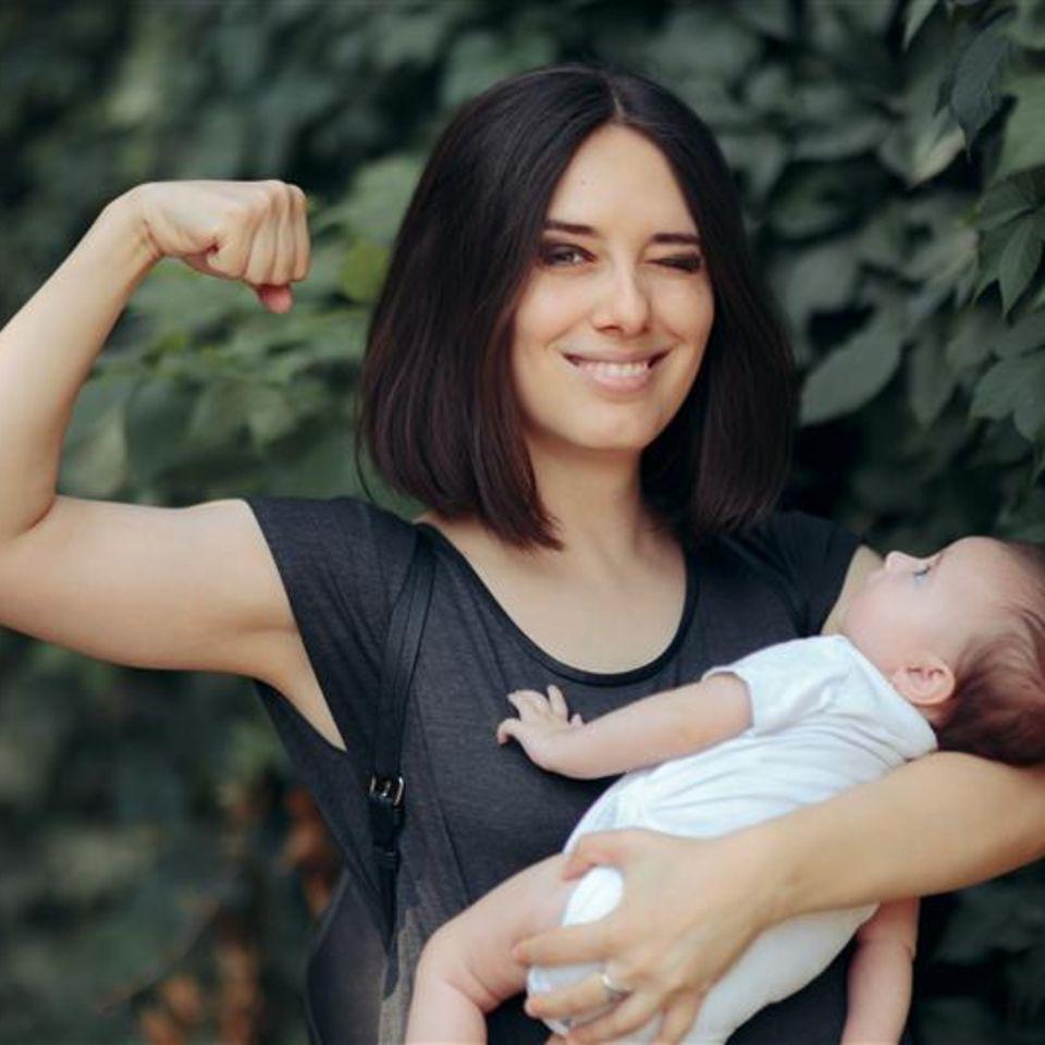 Job und Familie: Frau mit Baby im Arm verdeutlicht Power und Stärke