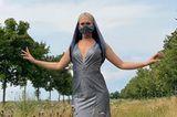 Saran Knappik steht in einem Abendkleid und ungwöhnlicher Maske in einem Feld.