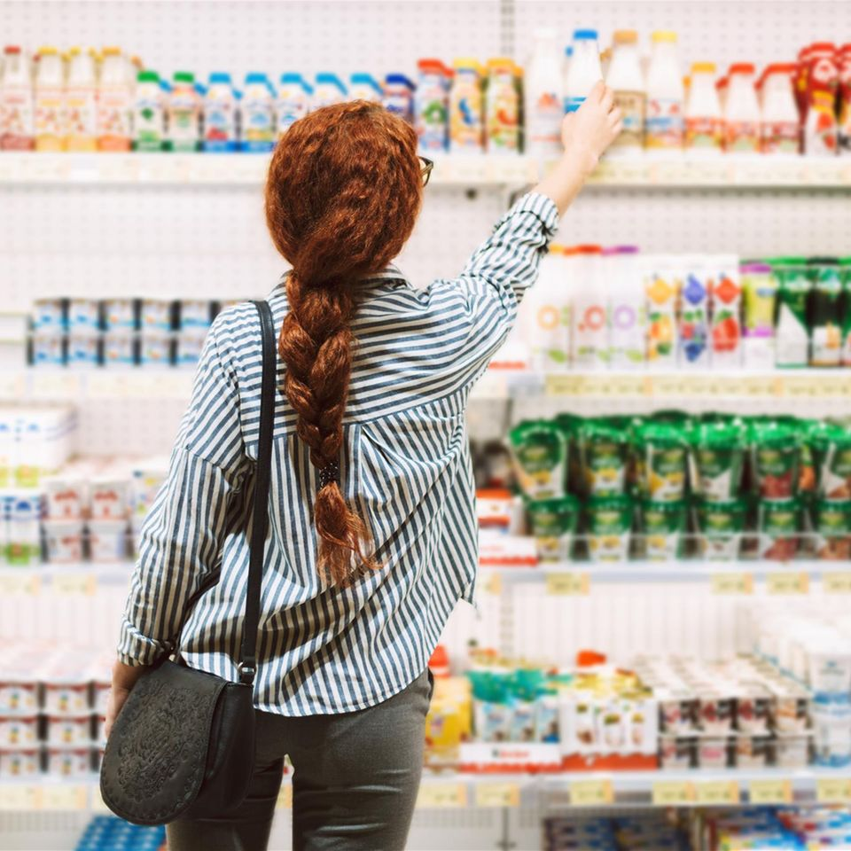 Frau steht vor dem Kühlregal im Supermarkt