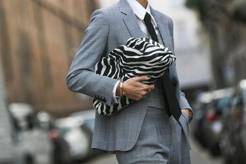 Unisex-Look: gekleidet im Anzug mit Handtasche