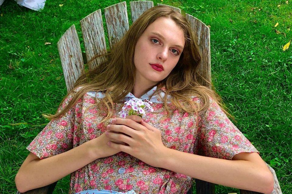 Ariel Nicholson lehnt sich auf einem Holzstuhl zurück und hält dabei einen kleinen Blumenstrauß in der Hand.