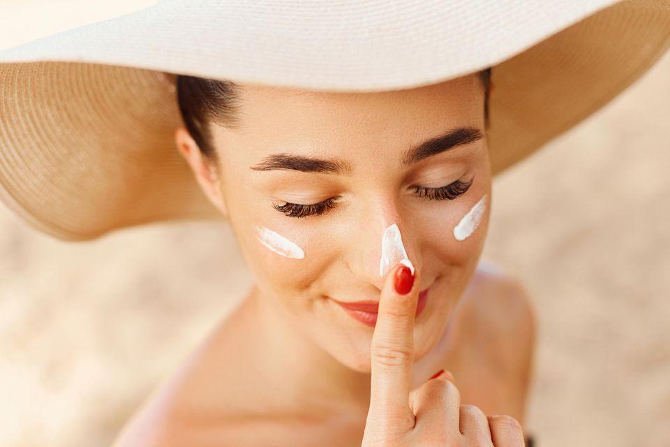Blasser Teint: Frau mit Hut trägt Sonnencreme auf
