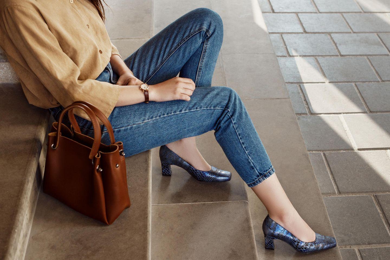 You go girl: Frau in Bluse mit Jeans und Heels