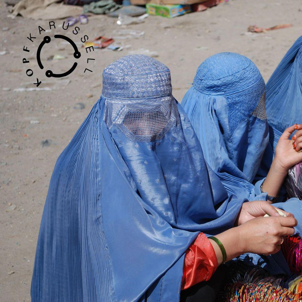 drei afghanische Frauen in traditionellen blauen Burkas schauen sich Armreifen an