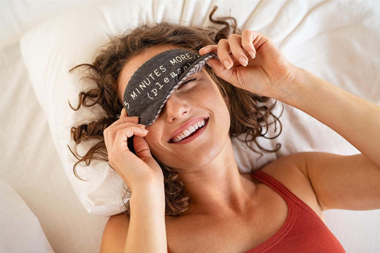 Dunkle AUgenringe: 7 Treatments im Check: Frau mit Schlafmaske im Bett