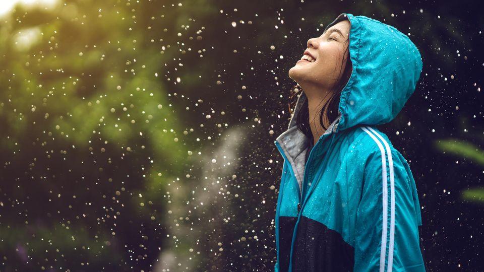 Horoskop: Eine fröhliche Frau im Regen