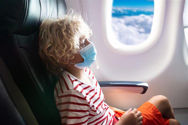 Southwest Airlines: Kind sitzt mit Mundschutz am Fenster im Flugzeug