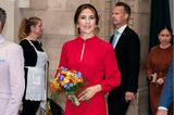 """Bei der offiziellen Eröffnung von """"Copenhagen 2021"""" in Verbindung mit WorldPride und EuroGames im Rathaus in Kopenhagen zeigt sich Prinzessin Mary in einem Outfit, bei dem einfach alles stimmt.Zum knallig roten Mididress kombiniert sie spitze Wildleder-Heels im gleichen Farbton. Der Blumenstrauß, den sie vermutlich geschenkt bekommen hat,fügt sich perfekt in das Gesamtbild ein und scheint fast zum Outfit dazuzugehören. So kommt auch bei tristem Wetter Sommer-Feeling auf!"""