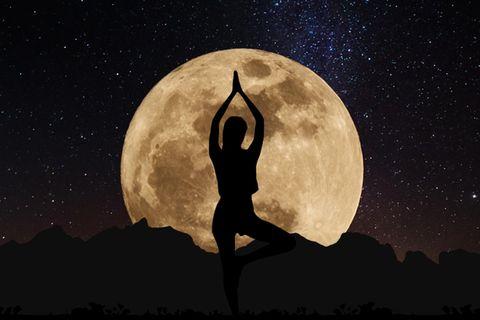 Horoskop: Umriss einer Frau, die vor dem Vollmond Yoga macht