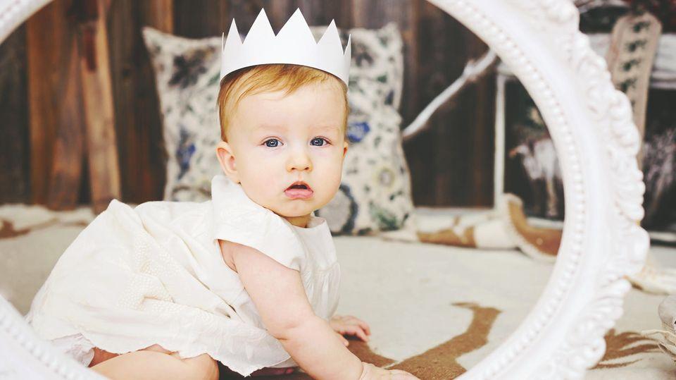 Ein Baby hat eine Krone auf sitzt in einem runden Rahmen und schaut in die Kamera.