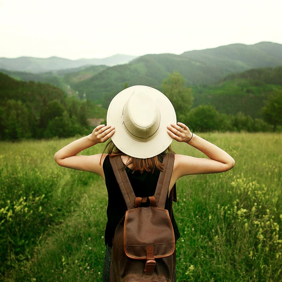 Nachhaltig reisen: Frau mit Hut in grüner Umgebung