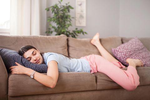 Schlafen bei Hitze: Frau schläft auf dem Sofa