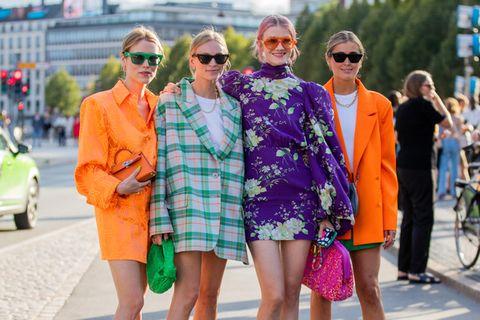 Vier Frauen posieren in ihren Outfits für die Fotografen.