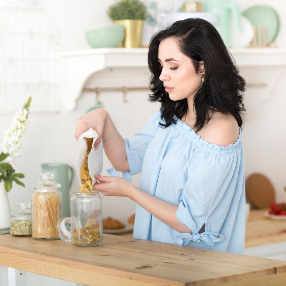Nachhaltiger leben: Frau füllt Produkte in der Küche auf