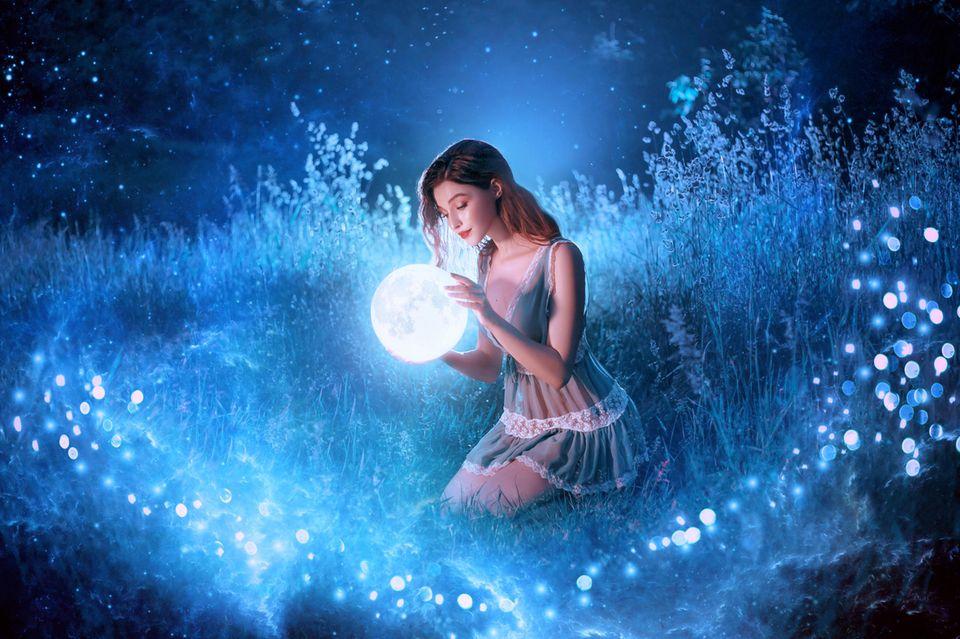 Horoskop: Frau im mystischen Sternenlicht hält blauen Planeten vor sich