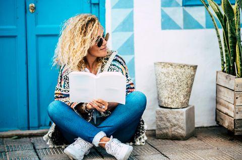 Psychologie:Eine lockige, blonde Frau mit Sonnenbrille und Buch