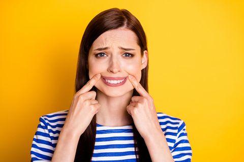 Dating-Chamäleon: Frau zieht gequält die Mundwinkel nach oben