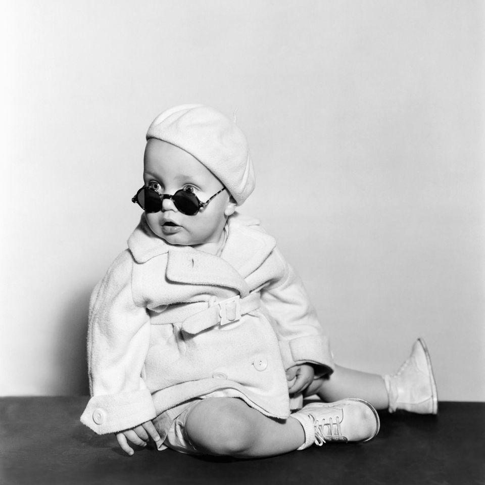 Ein Kleinkind mit einem Mantel bekleidet und einer großen Sonnenbrille sitzt auf dem Boden und schaut in die Kamera