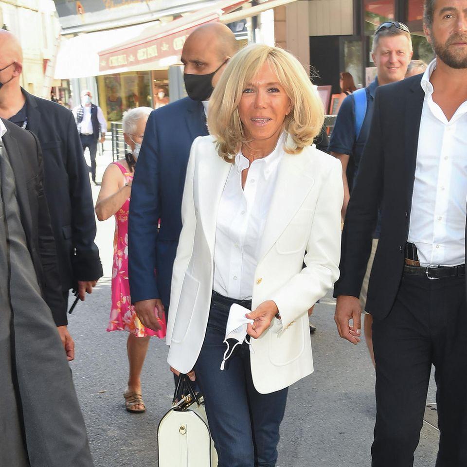 Wenn Französinnen styletechnisch eines können, dann mit ihrer lässigen Eleganz punkten. Das jüngste Beispiel: Brigitte Macron, die mit ihrem Look den perfekten Stilbruch aus sportlich und elegant meistert. Dafür kombiniert die Première Dame zu einemweißen Blazer und schicker BlusecooleJeans und Sneaker. Die Liebe zum Detailspiegelt sich in ihrer Tasche wider, deren goldene Applikationen perfekt zu den Blazerknöpfen passen. Très bien!