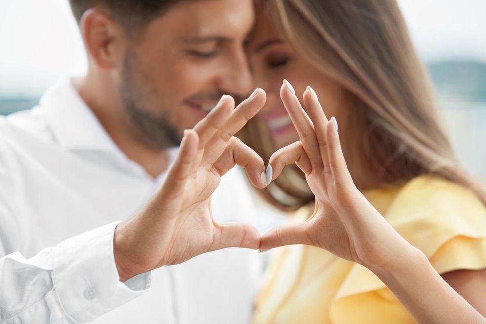 Ein Pärchen schmiegt sich verliebt aneinander und formt aus den Händen ein Herz, das im Vordergrund des Bildes steht.