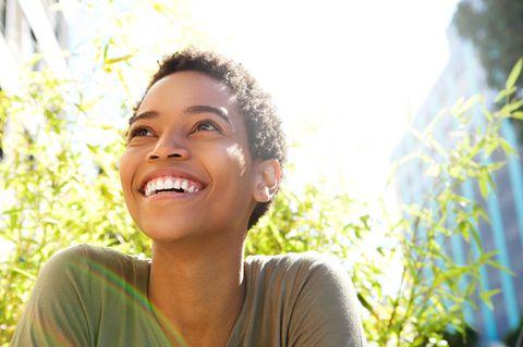 Horoskop: Junge Frau lacht glücklich in die Sonne