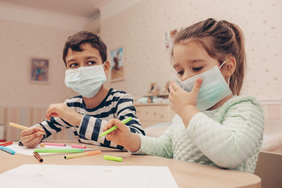 Zwei Kinder beim Malen mit medizinischen Masken.