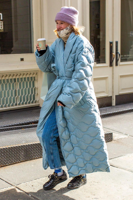 Steppmantel: Frau trägt einen blauen Oversize-Steppmantel mit Taillengürtel