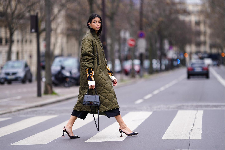 Steppmantel: Frau trägt einen dunkelgrünen langen Steppmantel