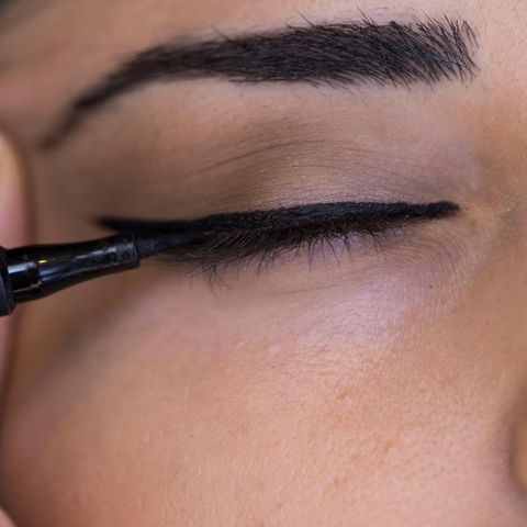 Eyeliner: Frau trägt schwarzen Eyeliner auf