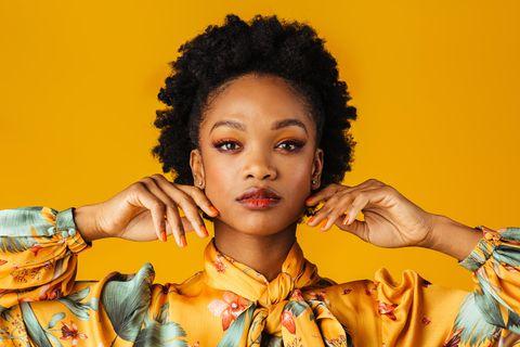 Eine Schwarze Frau trägt ein orangefarbenes Outfit und Nagellack