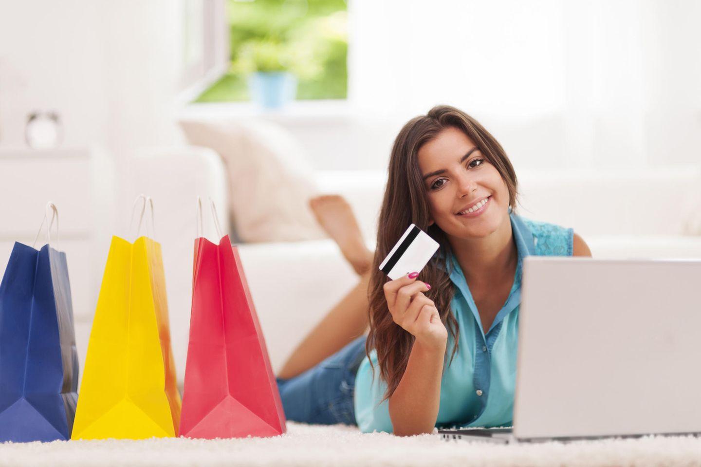 Frau mit Kreditkarte, Laptop und Einkaufstüten, Online-Shopping