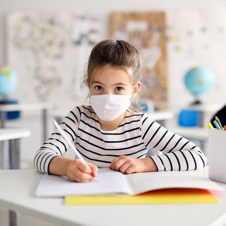 Ein junges Mädchen trägt in der Schule eine Maske.