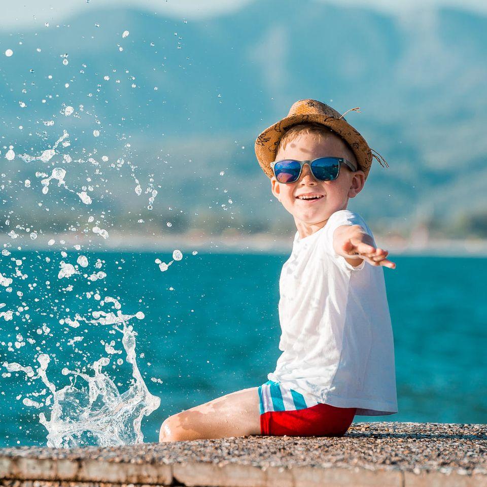 Ein Junge sitzt an einem Steg aus Stein und spritzt mit seinen Beinen im Wasser