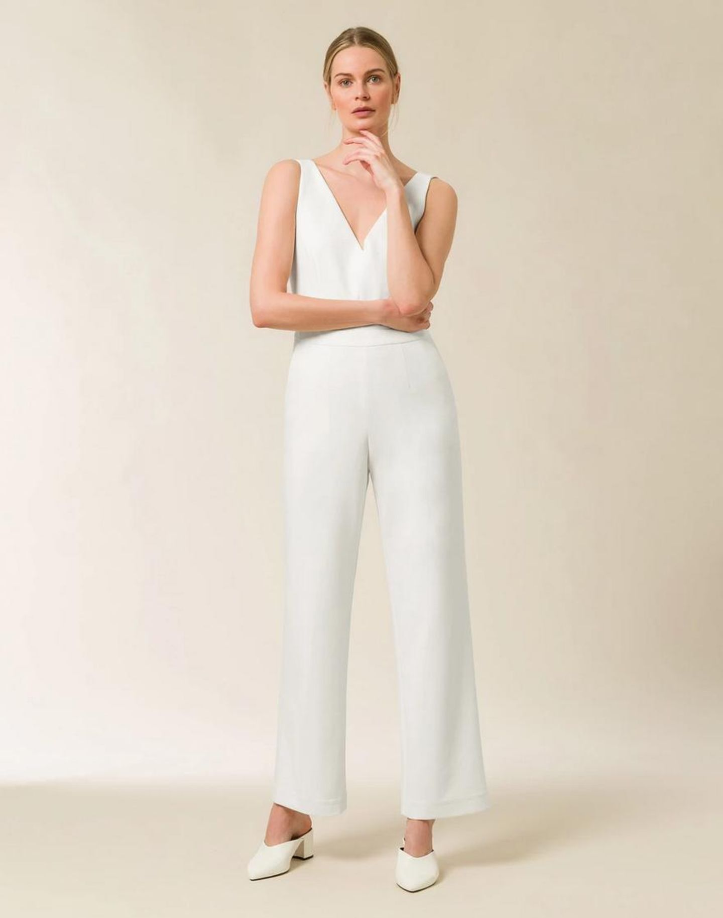 Ein Model präsentiert einen weißen Jumpsuit.