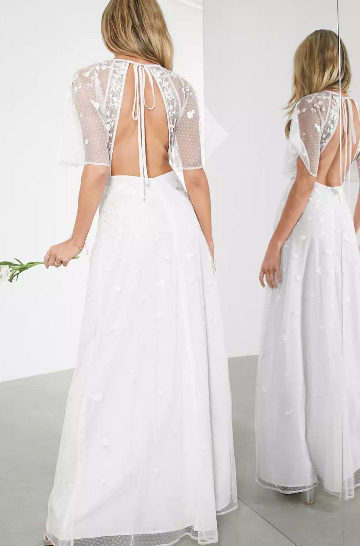 Ein Model präsentiert ein Brautkleid und zeigt dabei den Rückenausschnitt des Kleides.