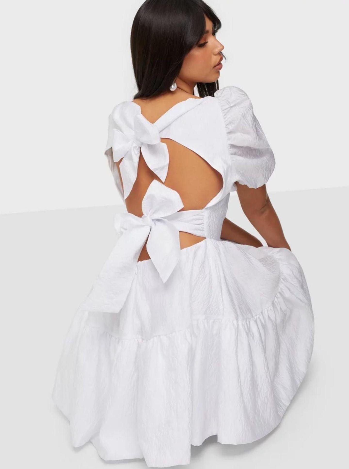 Ein Model kniet und präsentiert den Rückenausschnit ihres Kleides.
