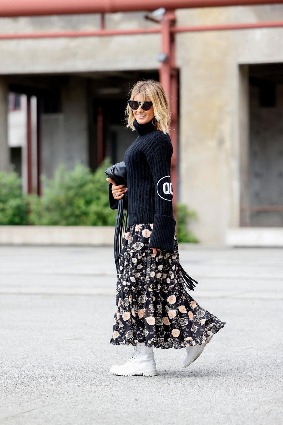 Blumenrock: Frau trägt einen schwarzen Pullover und einen Rock mit Blumenmuster