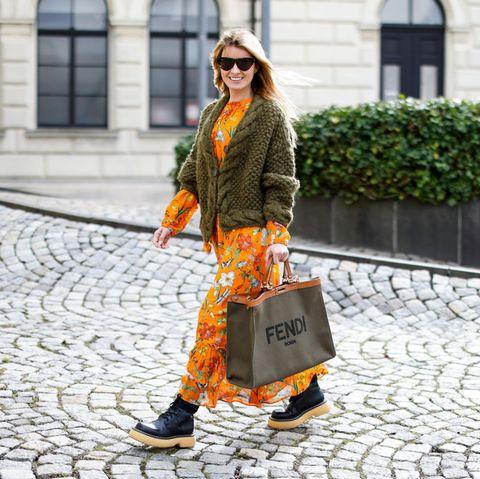 Blumenkleid: Frau trägt ein orangenes Kleid mit Blumenmuster