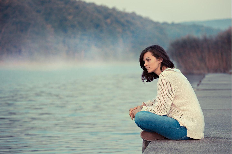 Frau schaut nachdenklich auf einen See