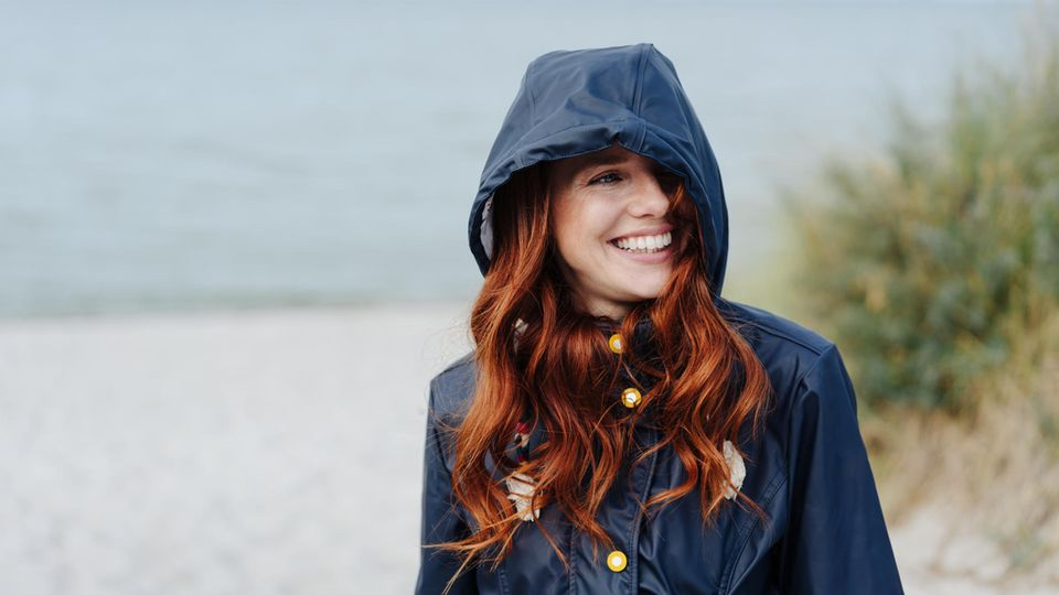 Horoskop: Eine fröhliche Frau am Strand
