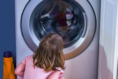 Ein Kind sitzt vor der Waschmaschine und wartet bis sie fertig ist.
