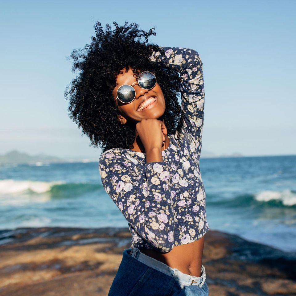 Psychologie: Glückliche Schwarze Frau am Meer