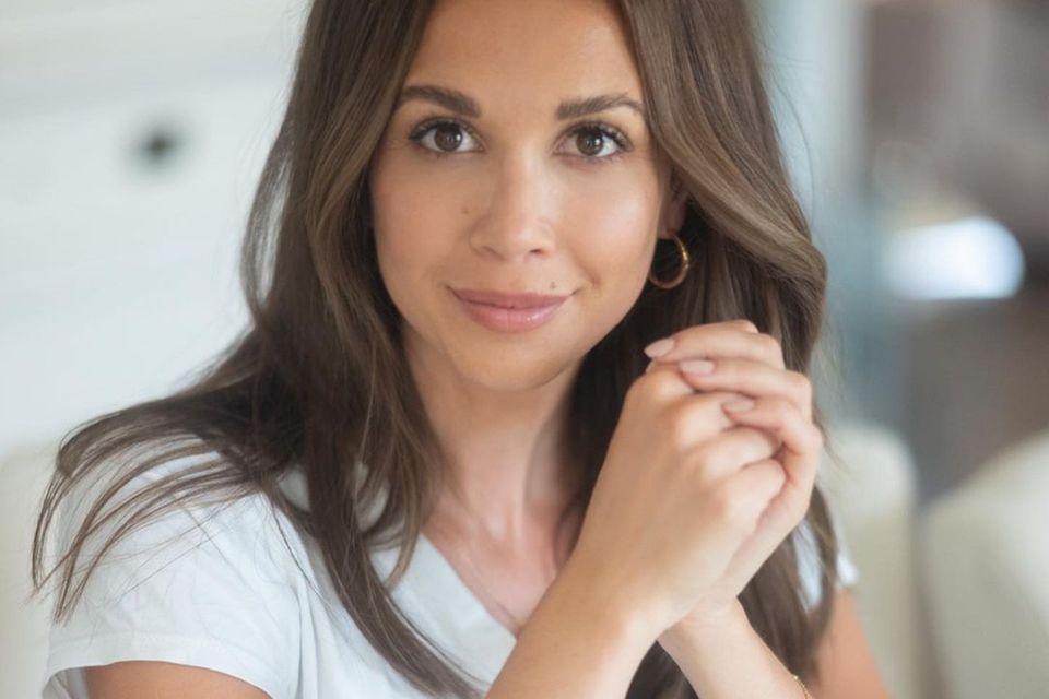 Mandy Capristo sitzt an einem Tisch und schaut in die Kamera.