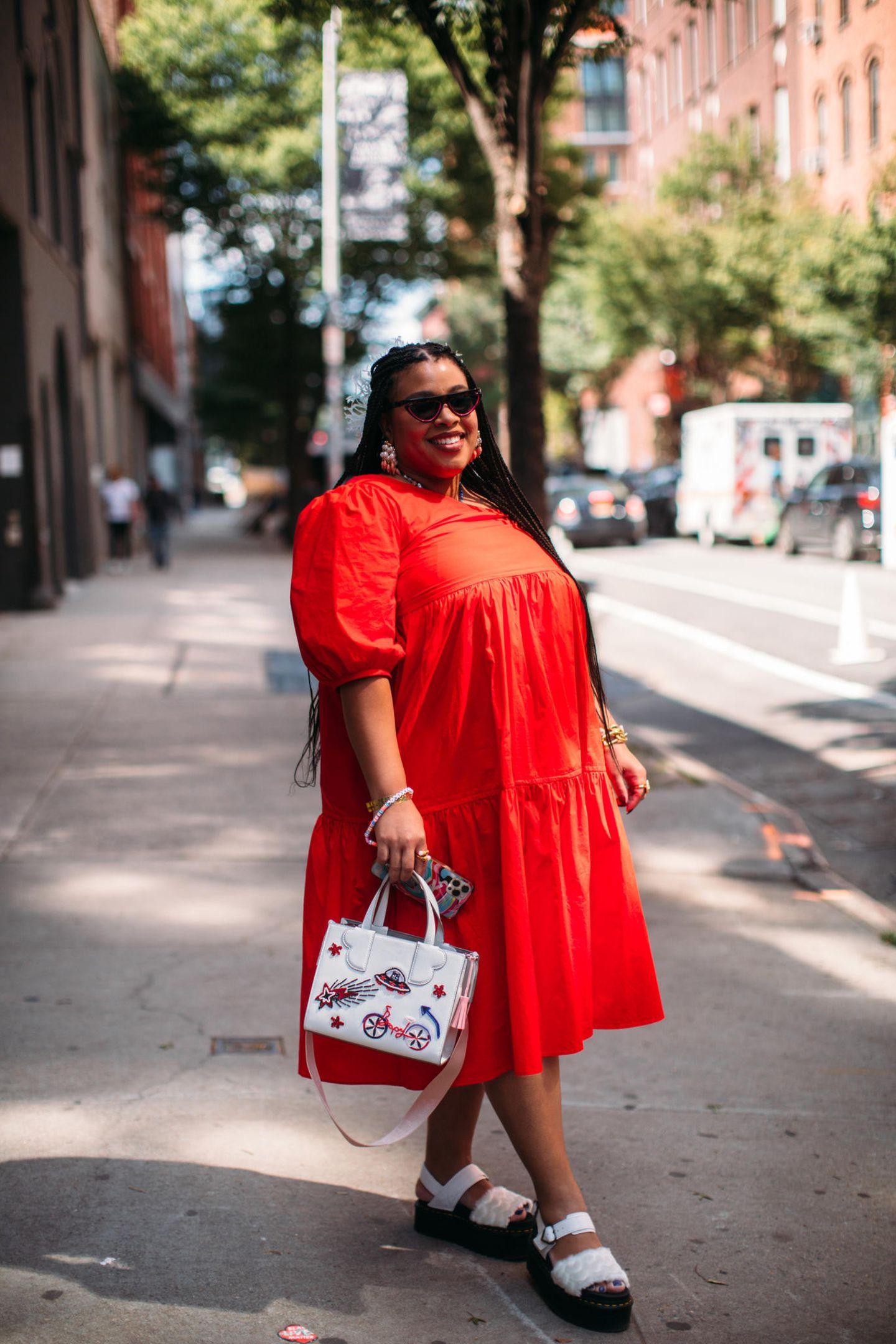 ... beweist diese Influencerin in ihrem knalligen Puffärmel-Kleid. Die weißen Accessoires mit roten Details ergänzen ihren Look perfekt.