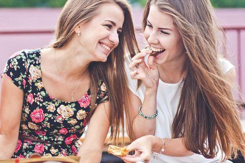 Zwei fröhliche Frauen essen Schokolade.