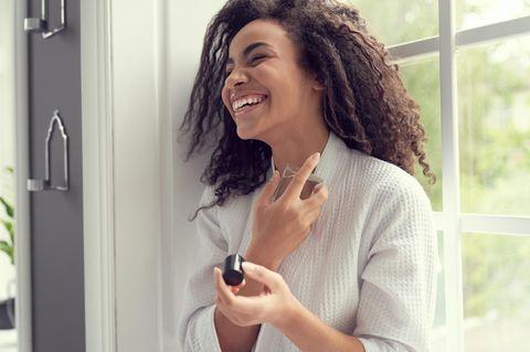 Parfum und Persönlichkeit: Frau lacht und hält ihren Lieblingsduft in der Hand